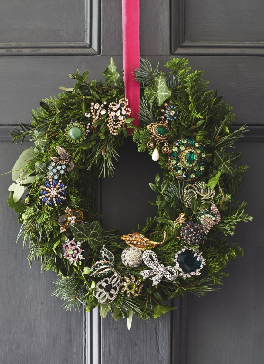 A festive wreath hangs on a dark grey front door. The wreath is peppered with sparkling antique and vintage brooches.