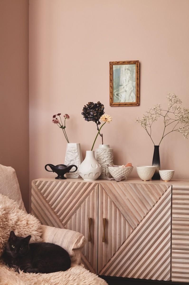 Multiple vases sit on a didebaord
