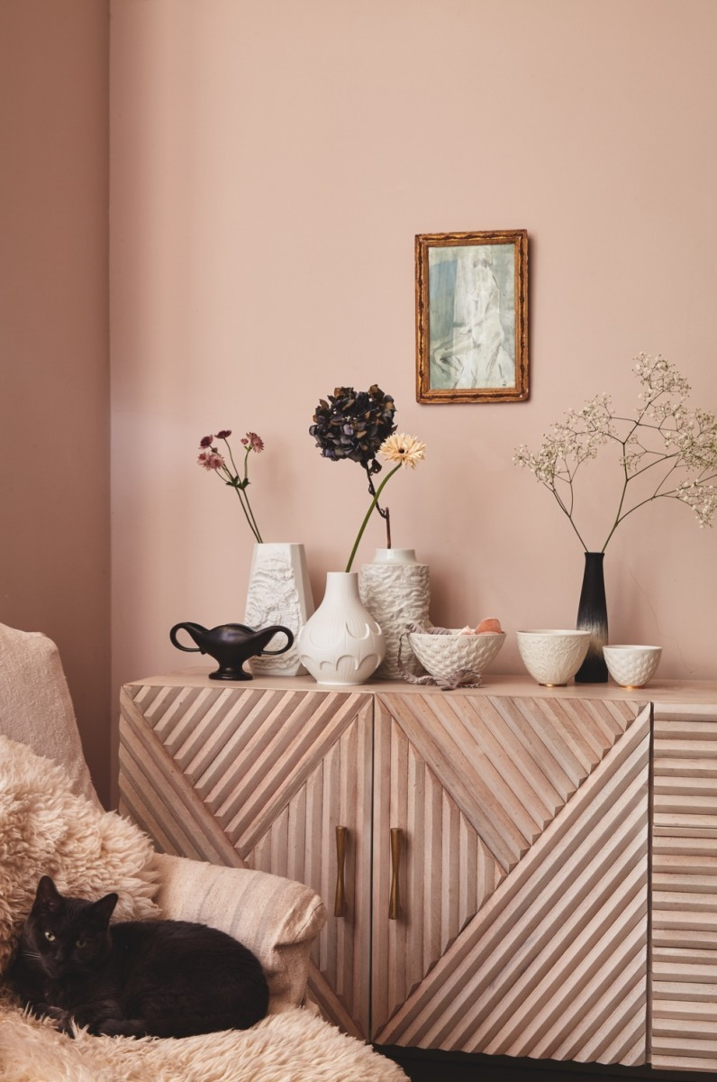 Multiple vases sit on a blush pink sideboad