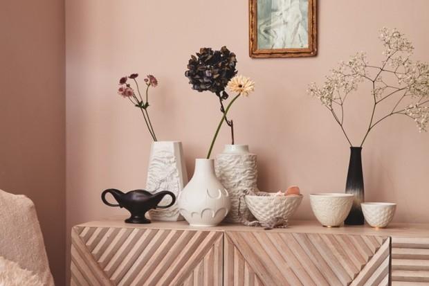 Multiple vases sit on a blush pink sideboad