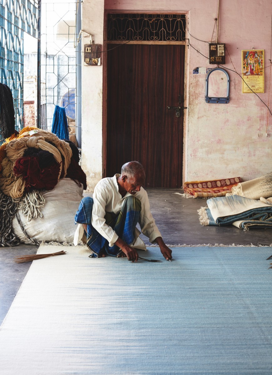 A craftsman weaves a rug in India