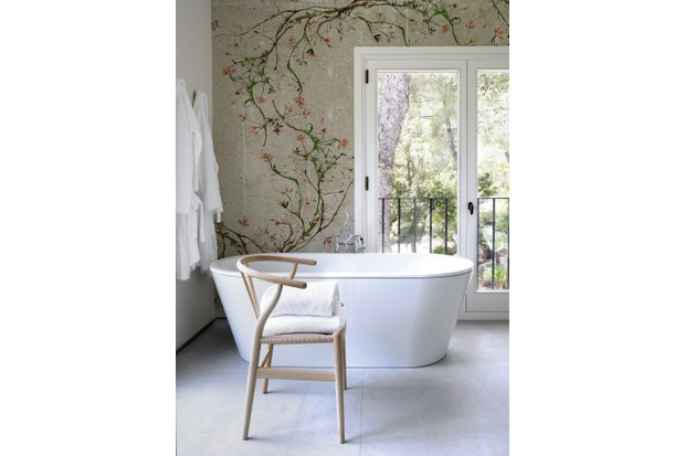 A contemporary white bath in front of chinoiserie wallpaper