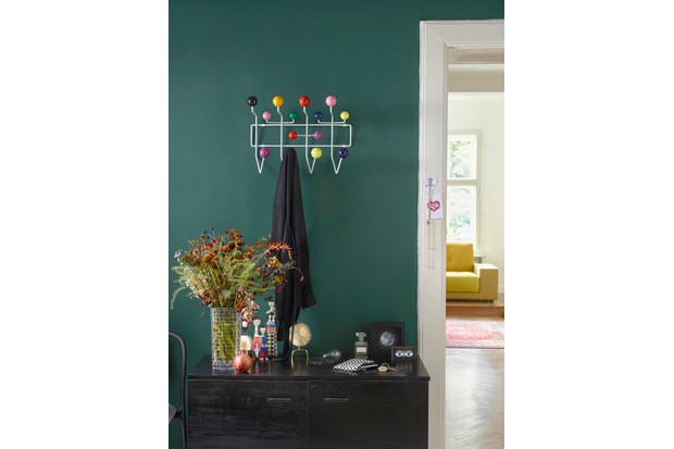A colourful Eames Hang it all on a bright teal wall beside a bunch of wildflowers