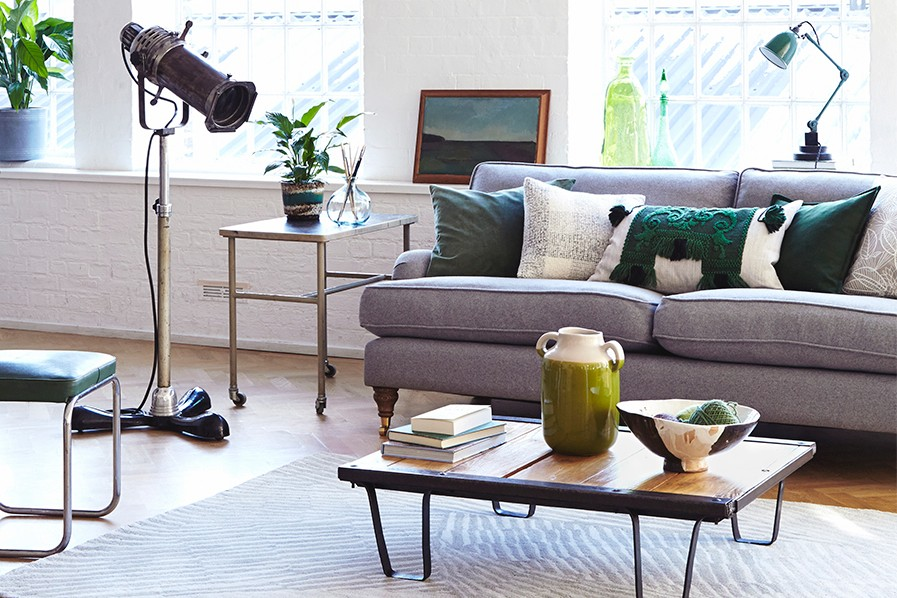 A wool sofa sits against strong vintage industrial furniture