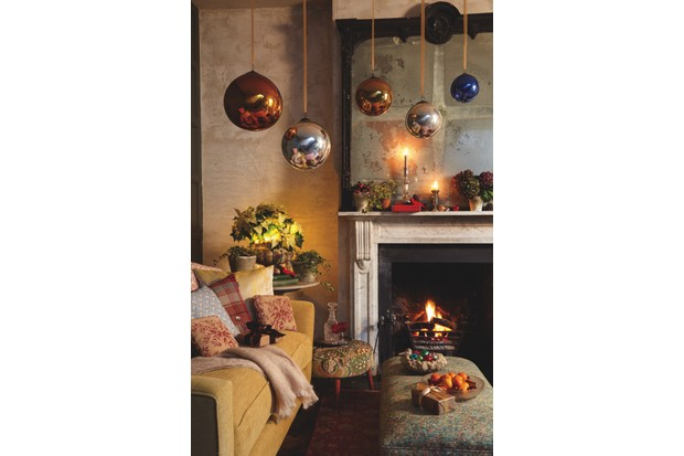 A selection of antique witch balls hung above a fireplace