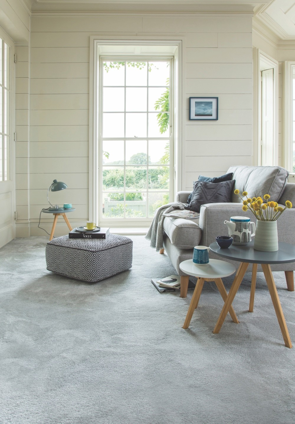 A Scandinavian-style living room with grey carpet, a grey sofa and stacking glass side tables