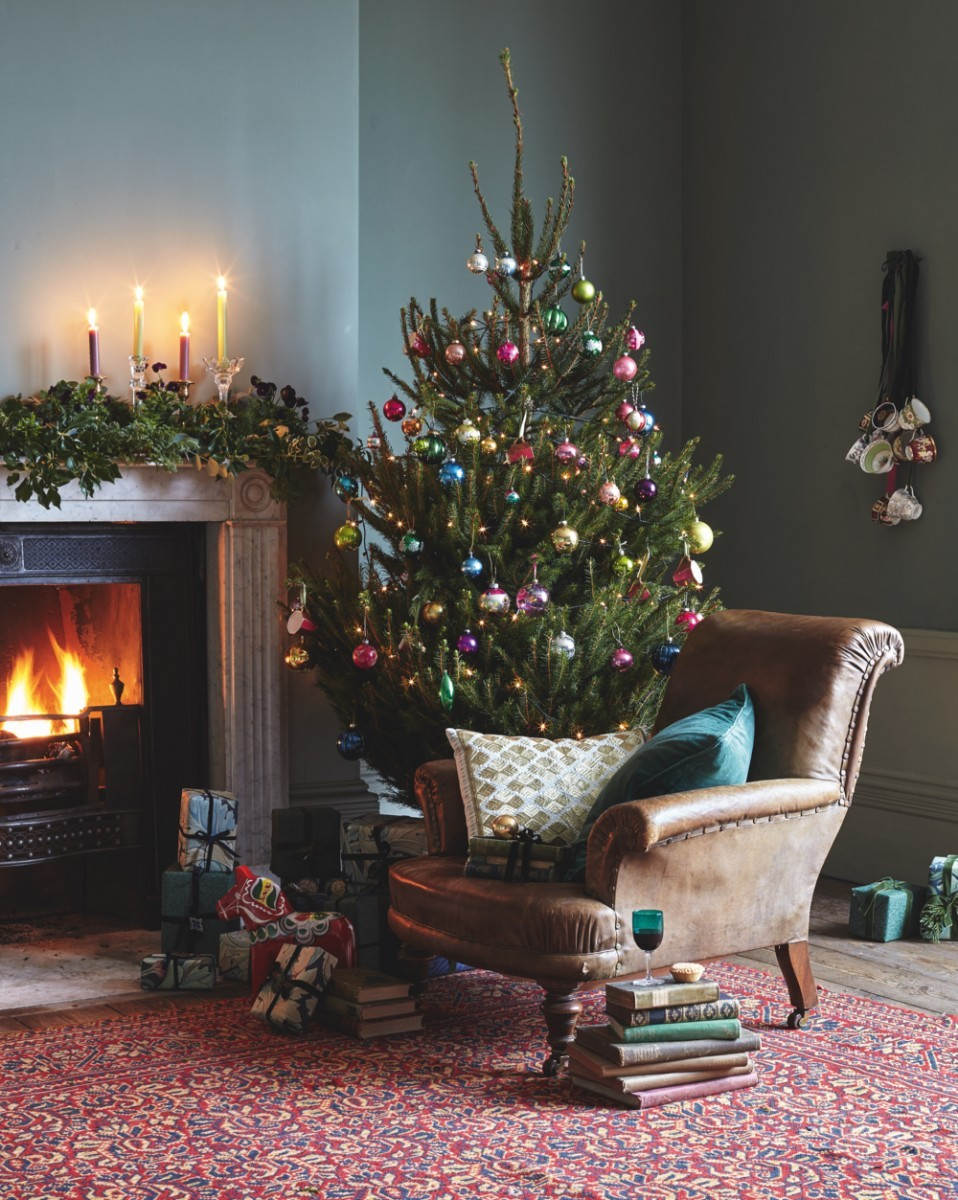 A cosy living room in a Victorian house with a roaring fire and a real Christmas tree laden with colourful antique and vintage baubles.