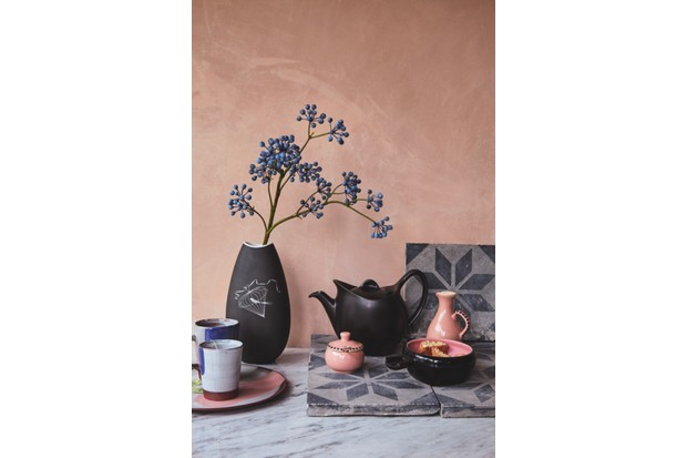A black teapot and vase sit atop vintage tiles against a blush pink wall