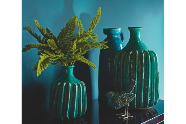 Dark teal ceramic vases filled with ferns