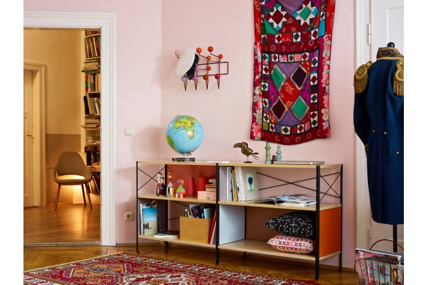 A red Eames Hang it All on a pale pink wall beside a vintage wall hanging