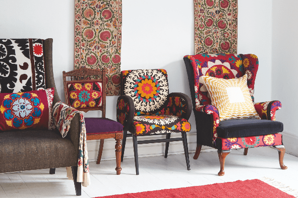 A Partiere suzani hangs on the wall above four vintage armchairs upholstered in vintage Suzani fabric