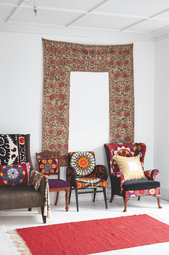A Partiere suzani hangs on the wall above some armchairs