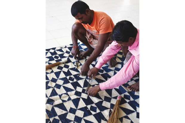 Two men trimming a rug