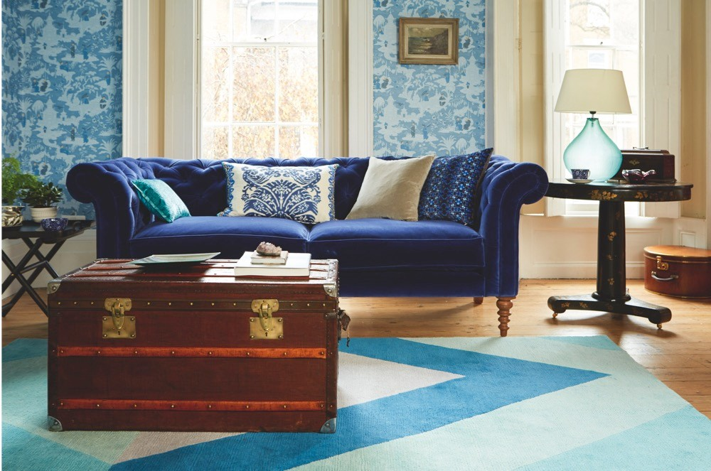 A brass and mahogany-coloured steamer trunk acts as a coffee table