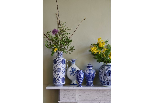 An array of blue and white ceramic vases filled with fresh flowers and foliage