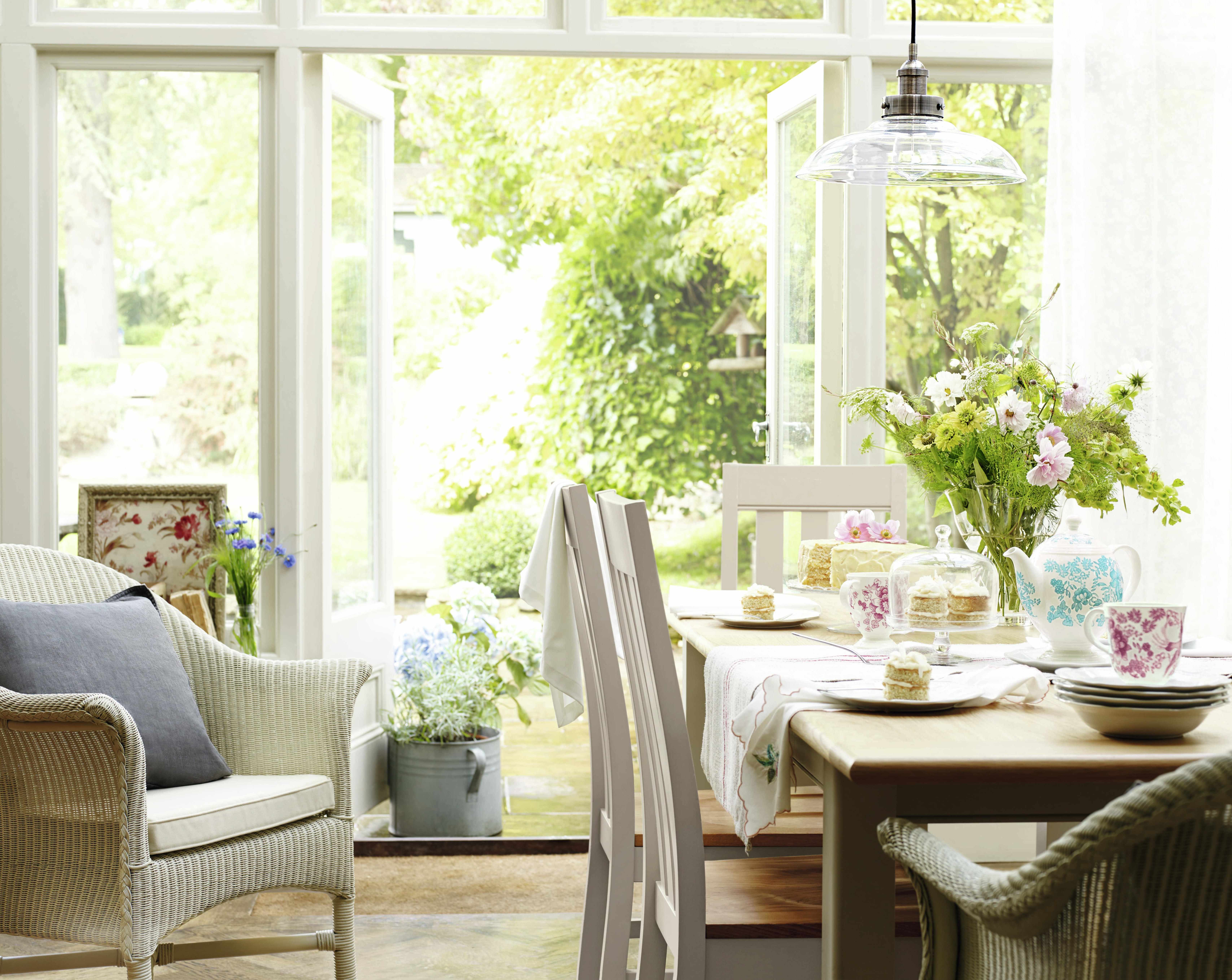 An airy conservatory space with a white dining table and chairs