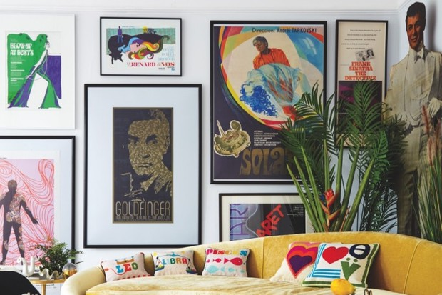 A wall of iconic film posters behind a curved yellow sofa