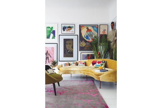 A wall of iconic film posters behind a curved yellow velvet sofa