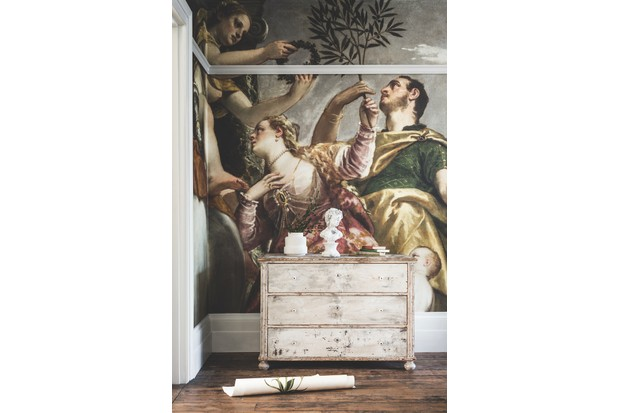 An oversized romantic wall mural behind a white-washed vintage chest of drawers