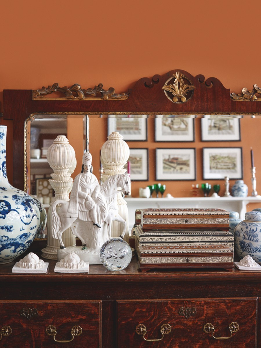A collection of different antiques sat in front of a mirror on a dresser
