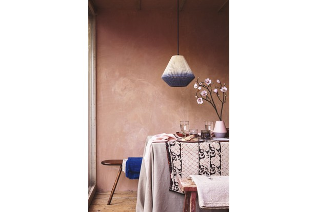 A dining table with benches, stools and a pink table cloth sits in front of a blush pink wall