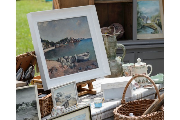 A table laden with antique curios and paintings at an outdoor flea market