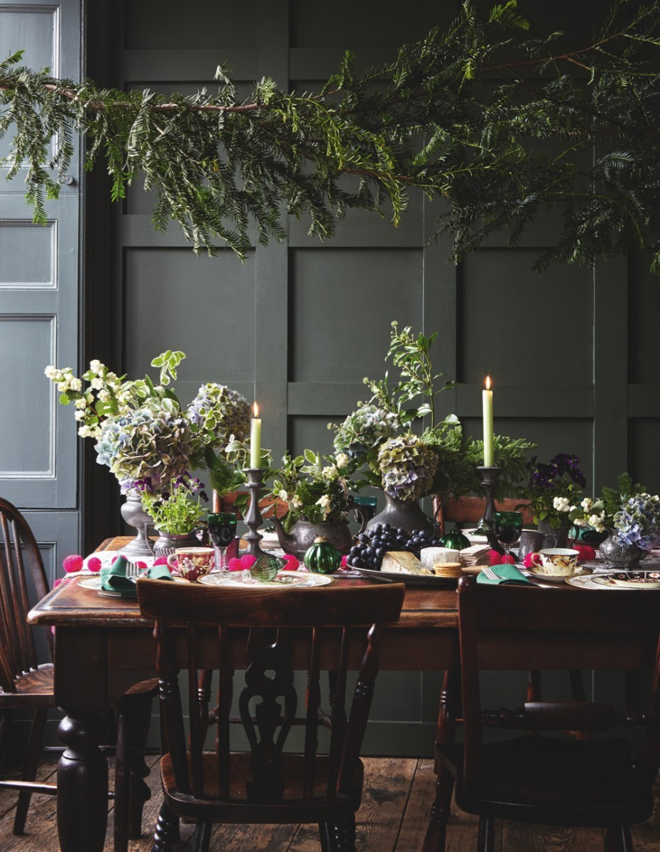 A Christmassy dining table in a dark grey living room. The table is decorated with antique pewter jugs filled with evergreen fronds and mophead hydrangeas. A string of pink neon pompoms brings some colour.