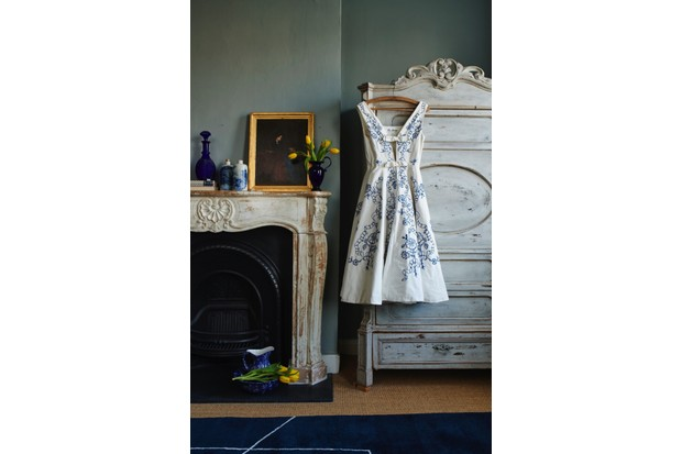 A white dress with a blue pattern on it hangs by a mantelpiece with a number of blue and white ceramics on it