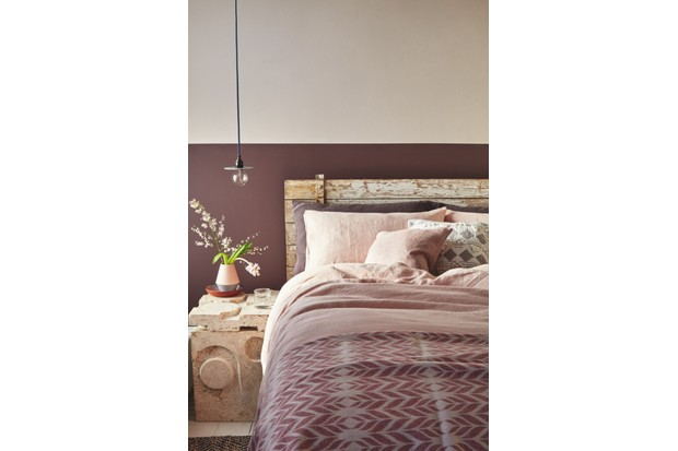 A washed wood double bed with pink bed linen against a two-tone purple and white wall