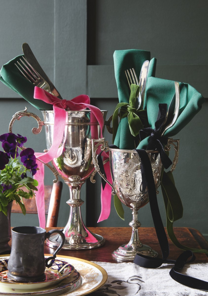Two antique silver goblets used as place settings. They are filled with a rolled linen napkin, antique cutlery and are tied with a velvet ribbon.