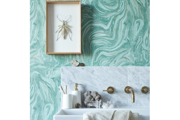 A marble sink decorated with fossils against malachite wallpaper and a framed insect