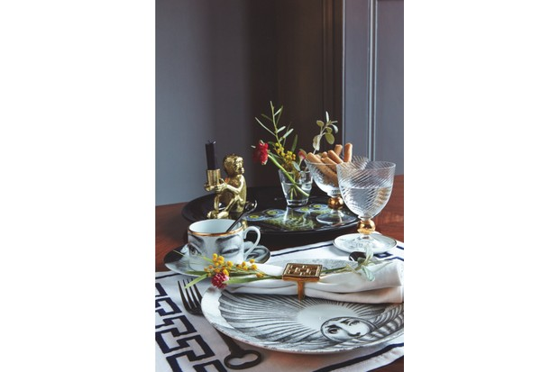 A brown breakfast table featuring a Fornasetti tray and tea cup, plus glasses filled with flowers and breadsticks