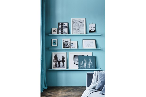 Ikea picture shelves against an aqua-blue wall displaying black and white photographs