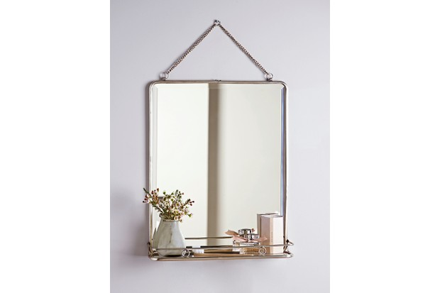 A vintage-style bathroom mirror hung by a rose gold chain