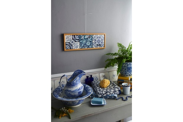 A basin on a mantelpiece below a framed set of English Delft tiles