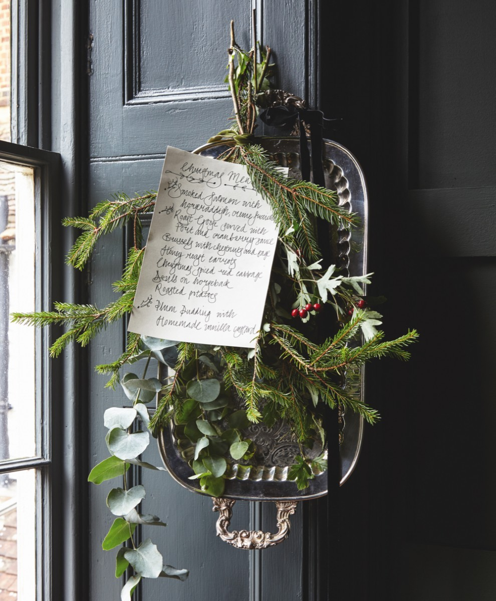 A handwritten Christmas dinner menu is tied to an antique silver tray with sprigs of mistletoe and evergreen.