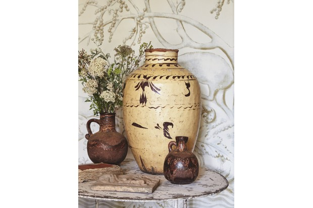 Different sized Terracotta storage pots filled with fresh greenery