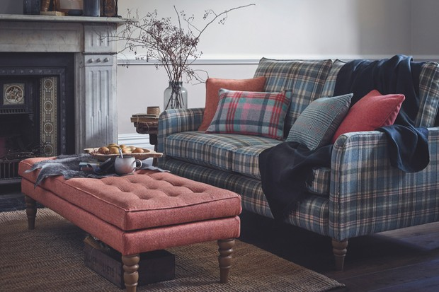 A traditionally upholstered footstool and sofa add wool and velvet detailing to a cosy living room style