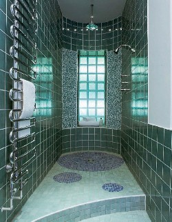 A shower room with green tiles on the wall
