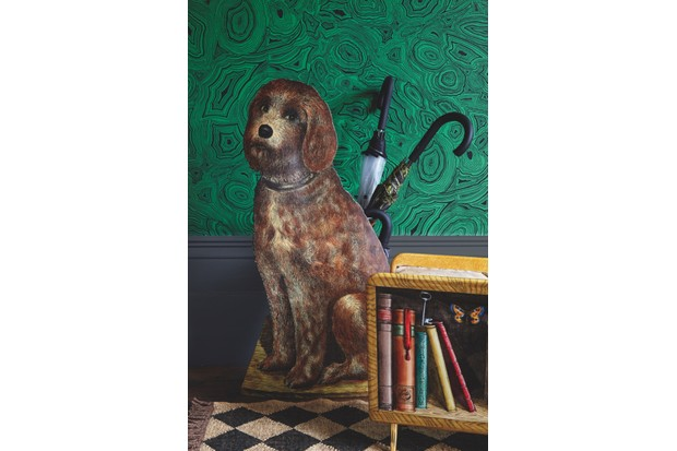 A Fornasetti umbrella stand in the shape of a dog against green malachite wallpaper