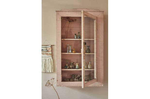 Clay coloured walls with a similar coloured glass cabinet