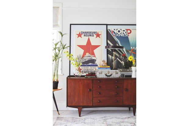 Framed posters leaning against a wall on top of a teak mid-century sideboard