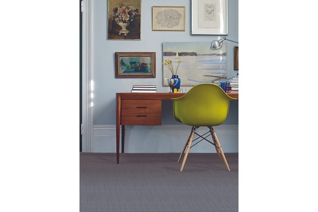 A gallery wall of paintings above a mid-century teak desk and Eames chair