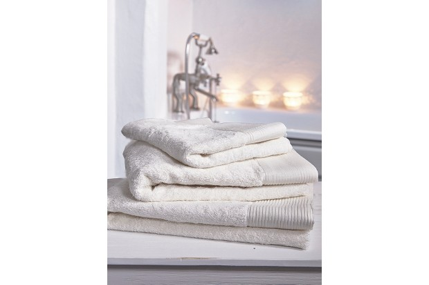 Soft white towels in a candle-lit bathroom