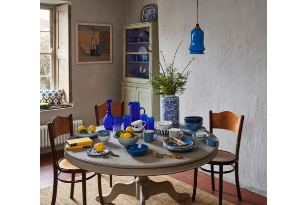 A kitchen table with a collection of blue and white ceramics on it