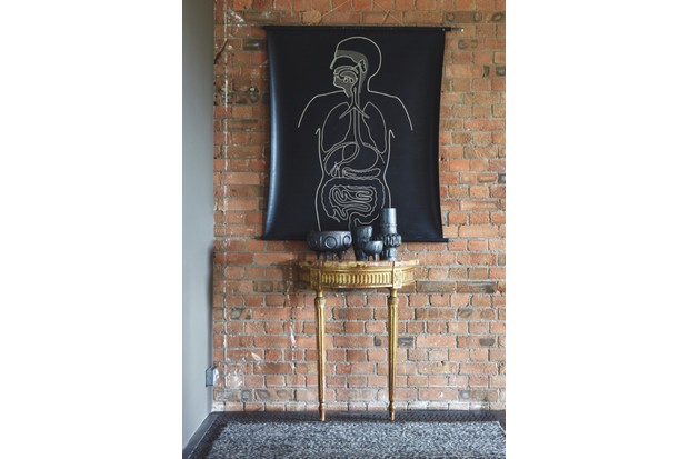 A black wall chart featuring a chalk outline of the human body on an exposed brick wall