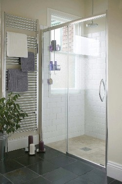 A sleek wetroom with white tiles on the walls of the enclosed shower