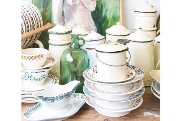 An array of antique enamelware on a table at a flea market