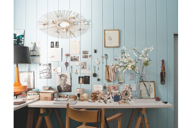 A pale blue office space. The walls are covered in frames and curios