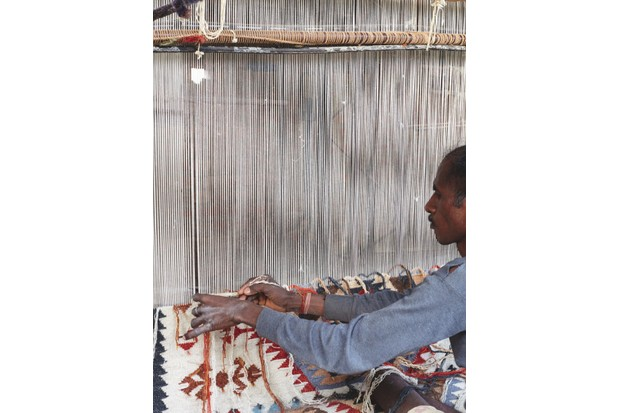 A man weaving the thread horizontally across the vertical thread